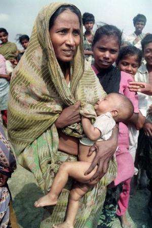 A woman carries her baby in Banskhali, Chittagong district, on May 9, 1991 in the aftermath of Bangladesh's worst cyclone in 20
