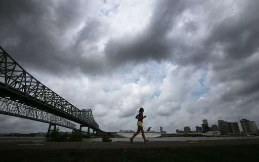 A woman jogs along a levee along the Mississippi River with the city skyline in the distance on May 16, 2015 in New Orleans, Lou