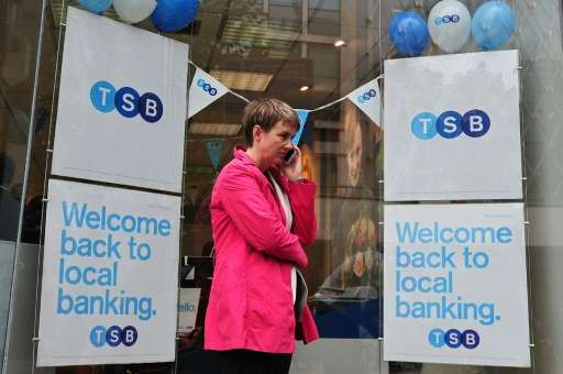A woman talks on her phone outside a TSB bank branch in central London