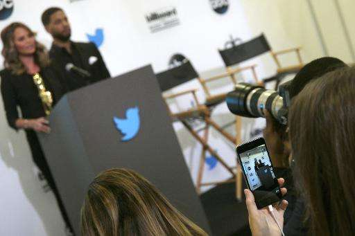 A woman uses the Twitter Periscope app on her smartphone to live broadcast a press conference in Santa Monica, California, April