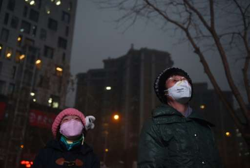 Beijing residents watch a giant video screen outside a shopping mall on a polluted day, on December 9, 2015