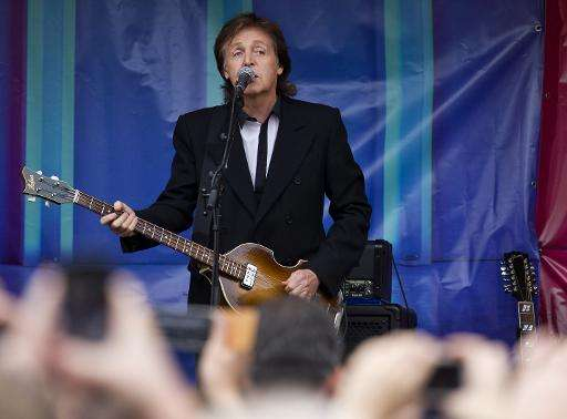 British musician Paul McCartney performs during an impromptu gig in Covent Garden in London on October 18, 2013