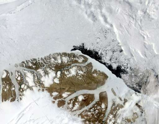 Broken ice floats in the Arctic Ocean off the northern coast of Greenland in this July 26, 2004 true-color NASA Terra satellite