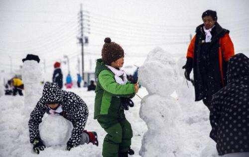 Children make snowmen in Iiyama city, Nagano prefecture on February 15, 2015