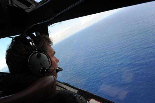 Co-pilot Brett McKenzie helps to look for objects during the search for missing Malaysia Airlines flight MH370, from a Royal New