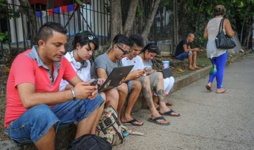 Cubans use their mobile devices to connect to the Internet via wifi in a street of Havana, on July 2, 2015