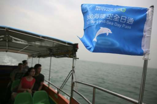 Customers on a boat tour to see the famous pink dolphins around the waters of Tai O in Hong Kong