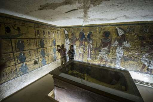 Egyptian archaeologists take pictures next to the sarcophagus of King Tutankhamun in his burial chamber in the Valley of the Kin