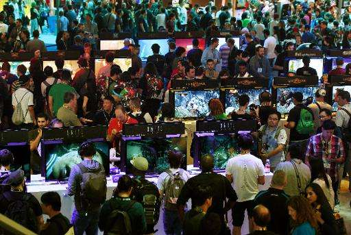 Gamers test new video games on display at the Sony Playstation area, on the opening day of the Electronic Entertainment Expo, kn