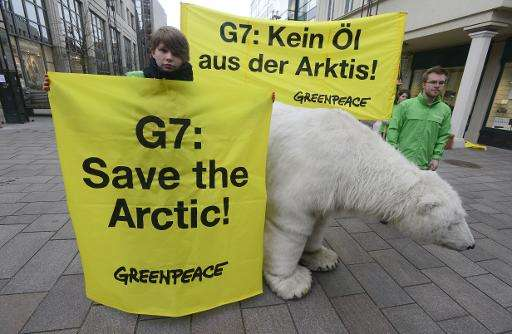 "Greenpeace activists pose with a mockup of a polar bear and with banners reading ""G7: Save the Arctic!"" and ""G7:"