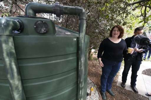 Homeowner Carrie Wassenaar, pictured November 4, 2015, shows off a new 1,320 gallon (5,000 liter) water tank designed to capture