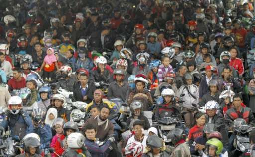 Hundreds of Indonesian passengers on motorcycles wait to board a ferry at Merak port in western Java island on July 15, 2015 to