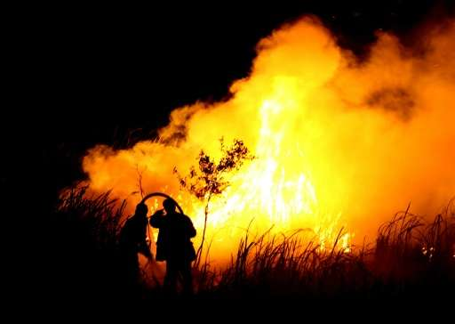 Indonesian men fight a fire in Ogan Ilir, southern Sumatra on October 22, 2015