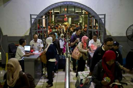Indonesian passengers enter the departure area of a packed train station in Jakarta on July 14, 2015