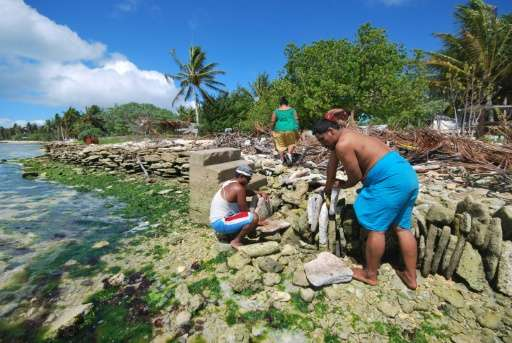 Inhabitants of Kiritimati coral atoll in Kiribati build a stone seawall to battle the rise in sea level caused by global warming
