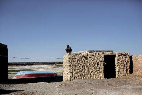 Iranian boys sit on the roof of a mud-house in the village of Adimi situated in the once exceptional wetlands of Lake Hamoon, no