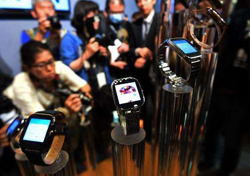 Journalists take photos of smart watches made by Taiwan's ASUSTeK Computer during the Computex trade show in Taipei, June 2, 201