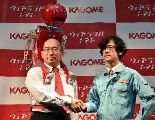 Kagome employee Shigenori Suzuki (L) wears the tomato dispenser, which was developed by Japanese artist Nobumichi Tosa (R)