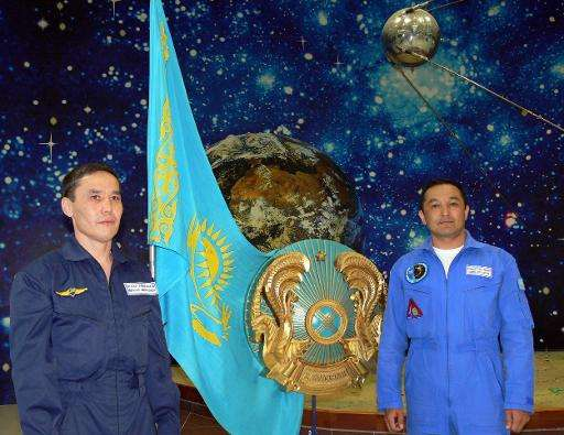 Kazakh cosmonaut candidates Mukhtar Aimakhanov (L) and Aidyn Aimbetov pictured next to their national flag and a model of the fi
