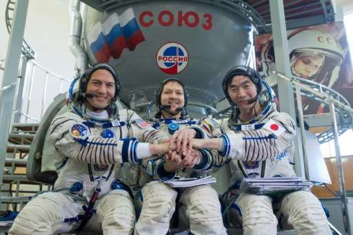 (left to right) Kjell Lindgren, Oleg Kononenko and Kimiya Yui pose for pictures after a pre-flight training session at the Gagar