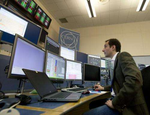 LHC operator Mirko Pojer watches screens at the CERN Control Center (CCC) in Meyrin, near Geneva
