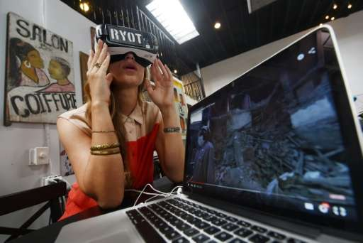 Molly Swenson, COO of RYOT, shows the virtual reality headset used to view their productions at their offices in Los Angeles, Ca