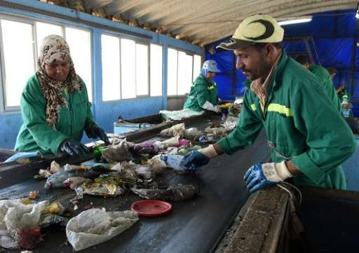 Moroccan labourers sort waste at the Attawafoq cooperative at Oum Azza industrial landfill in Ain Aouda