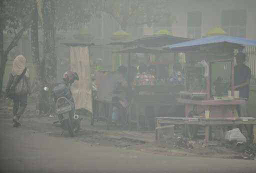People eat breakfast at a roadside stall shrouded in thick haze in downtown Palangkaraya, a city at the epicentre of Indonesia's