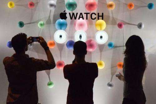 People stand before a window display of the Apple watch during the unveiling of the new and highly anticipated product at Saint-