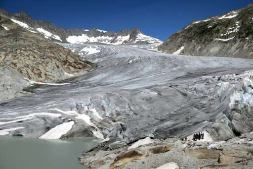 People stand next to the Rhone Glacier on July 14, 2015 which was wrapped with blankets as a protection from the sun near Gletsc