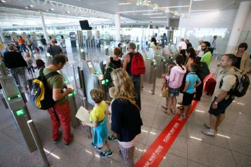 People wait to pass through new automated border control gates at Brussels Airport in Zaventem on August 3, 2015