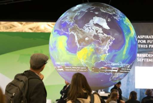 People watch the Earth globe at the COP21, the United Nations conference on climate change, in Le Bourget on December 10, 2015