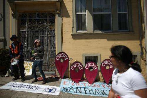 Protesters rally outside a San Francisco apartment building accused of evicting all its tenants to convert units into Airbnb ren