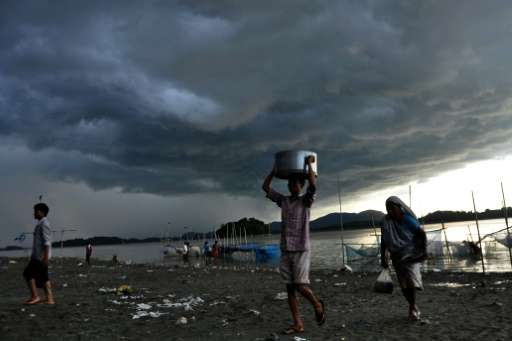 Rain clouds loom over the Brahmaputra river in Guwahati, capital of northeastern Assam state, India on August 27, 2013