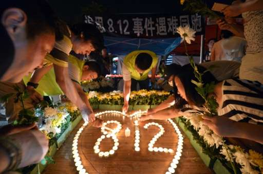 Residents lighting candles at the crossroads outside Tianjin Taida hospital at a vigil for the victims of the explosions at a ch