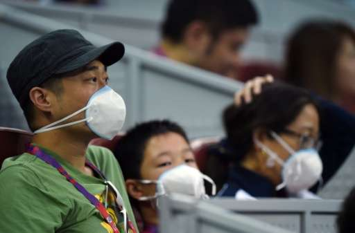 Spectators wear face masks as they watch a  match at the China Open tennis tournament in Beijing on October 5, 2015