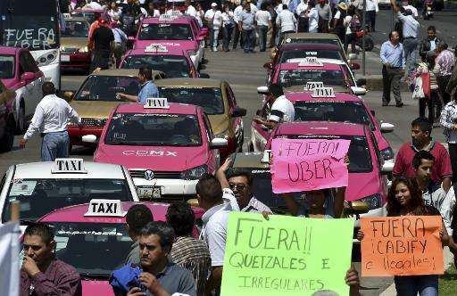 Taxi drivers take part in a protest against the private taxi company Uber for alleged unfair competition, in Mexico City on May