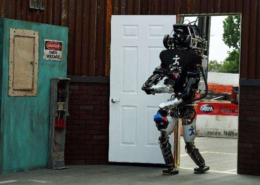 The robot named 'Running Man' developed by Team IHMC Robotics successfully opens a door during the finals of the DARPA Robotics