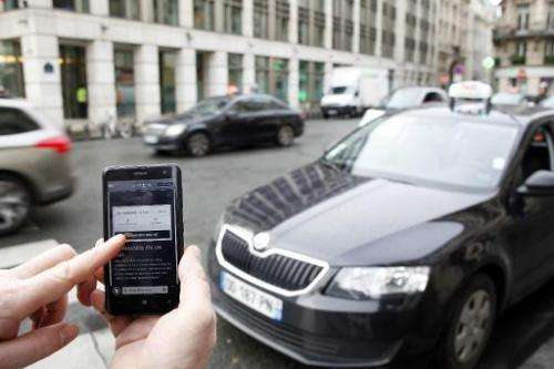 The Uber smartphone app is pictured on a smartphone in front of a taxi on December 10, 2014, in Paris