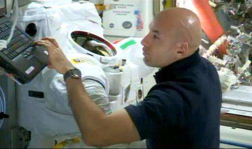 This NASA TV image shows Italian astronaut Luca Parmitano working next to his space suit, which experienced a water-in-helmet le
