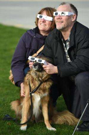 Two people and their dog wear protective glasses as they look towards a partial solar eclipse at the Pier Head in Liverpool, nor