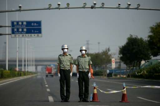 Two soldiers wearing face masks stand at a checkpoint in Tianjin near the site of the explosions at a chemical warehouse that hi