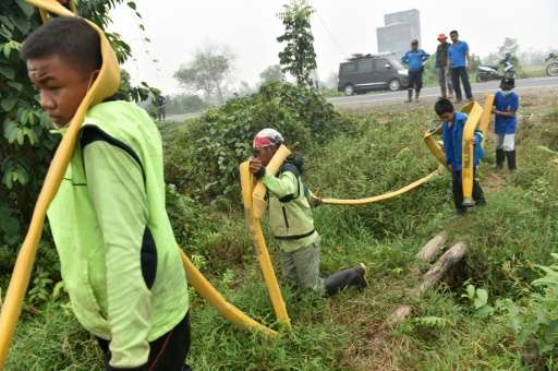 Volunteers carry hoses as they combat forest fires in Kuala Kapuas, Central Kalimantan