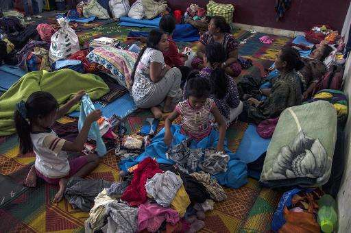 Women and children rest in an evacuation shelter set up following an eruption at Mount Sinabung in Kabanjahe village, in Karo di