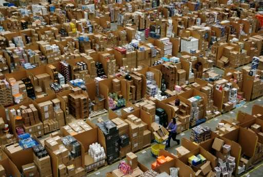 Workers walk along aisles of goods stored inside an Amazon.co.uk fulfillment centre in Hemel Hempstead, north of London, on Nove