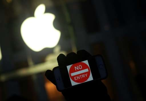 """An anti-government protester holding his iPhone with a sign """"No Entry"""" during a demonstration near the Apple store on"""