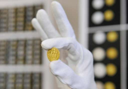 An employee of Romanian National History museum shows a golden coin in Bucharest on November 8, 2013