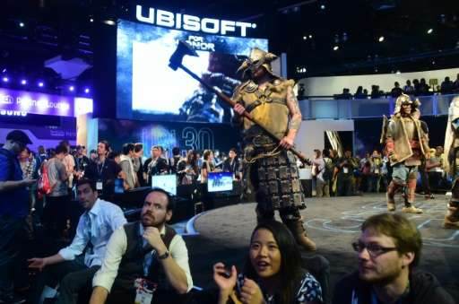 Gaming fans watch the screens as costumed characterizations from the game 'For Honor' by Ubisoft roam the stage during the 2016