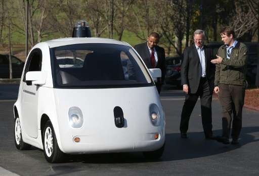 Google's Chris Urmson (R) shows a Google self-driving car to US Transportation Secretary Anthony Foxx (L) and Google Chairman Er