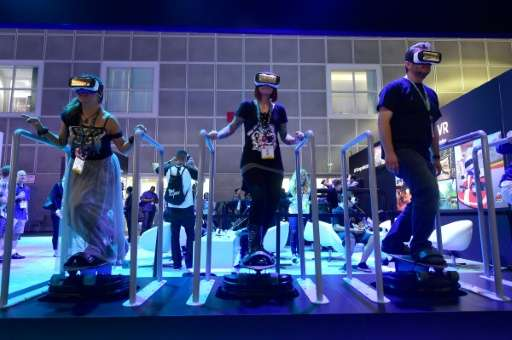 People 'skateboard' while sampling Samsung's Gear VR headsets powered by Oculus at E3 on June 15, 2016 in Los Angeles, Californi